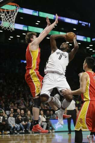 Andray Blatche of the Nets shoots over Omer Asik of the Rockets.