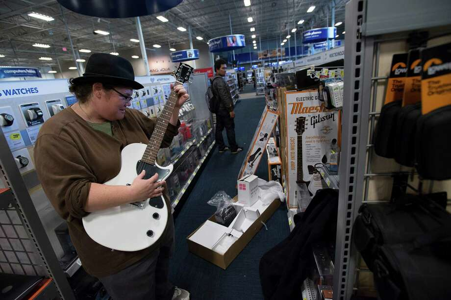 A shopper tries out a guitar at a San Francisco Best Buy. The chain's online price policy is changing. Photo: David Paul Morris / © 2013 Bloomberg Finance LP