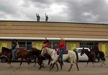 Construction workers wave to the Texas Independence Trail Ride as it travels...