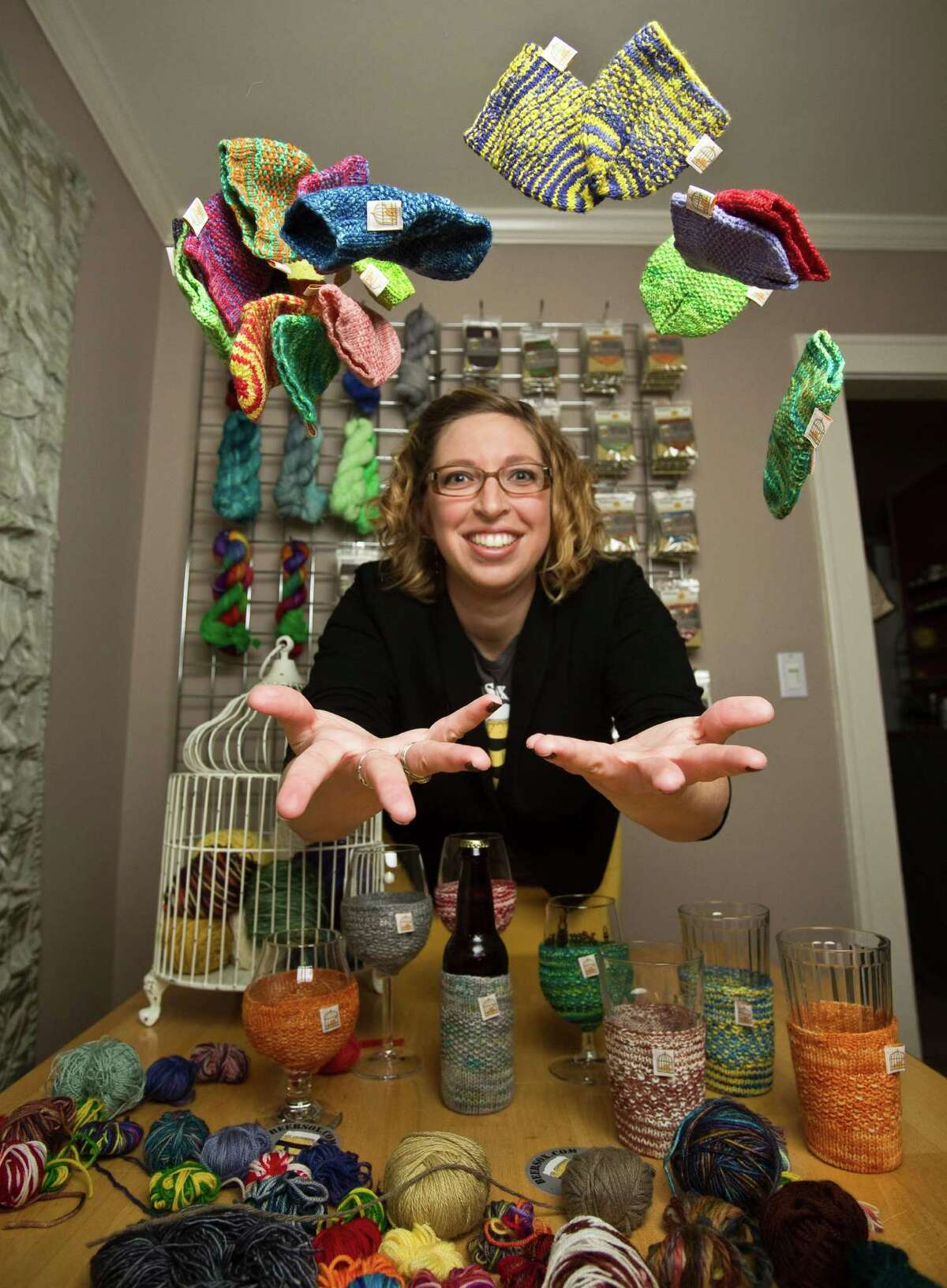 Katie Mahoney, owner of The Caged Yarn, has to juggle her regular job in the energy industry with her small business that makes hand-knit covers for beverage glasses and cans.Katie Mahoney, owner of The Caged Yarn, has to juggle her regular job in the energy industry with her small business that makes hand-knit covers for beverage glasses and cans.