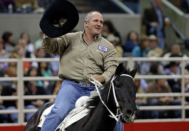 Tom Lewis takes a lap after posting the best time in steer wrestling , 4.5, during rodeo action at the AT&T Center on Friday, February 22, 2013. Photo: TOM REEL