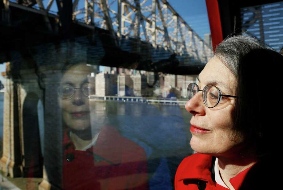 Janet Falk, public relations professional, rides the Roosevelt Island tramway with a Manhattan view behind her on Thursday, Feb. 21, 2013 in New York.  Falk applied for a public-relations job at a New York City law firm two years ago, but the recruiter told her she wouldn't be considered because she had been unemployed for more than three months, Falk said. (AP Photo/Bebeto Matthews) Photo: Bebeto Matthews