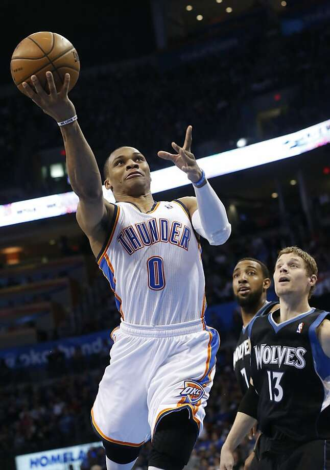 The Thunder's Russell Westbrook drives past Luke Ridnour to the hoop. Photo: Sue Ogrocki, Associated Press