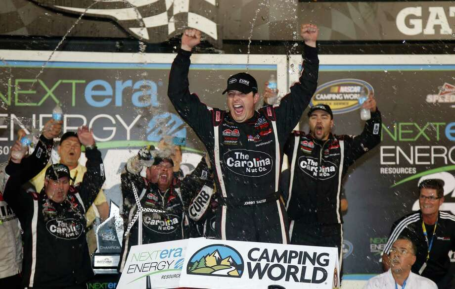 Johnny Sauter leads the cheers after winning the Camping World Trucks season opener Friday night. Photo: Chris Graythen, Staff / 2013 Getty Images