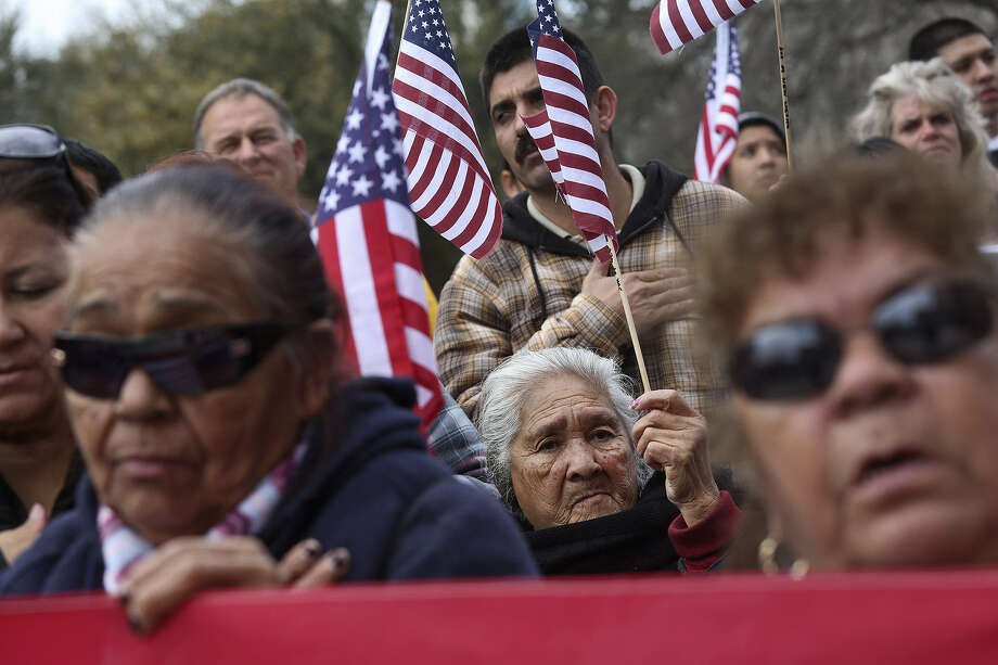 Enriqueta Breceda of El Paso (center) holds a flag during the singing of national anthem during the rally at the Texas Capitol after the march through the streets of Austin. Photo: Photos By Lisa Krantz / San Antonio Express-News