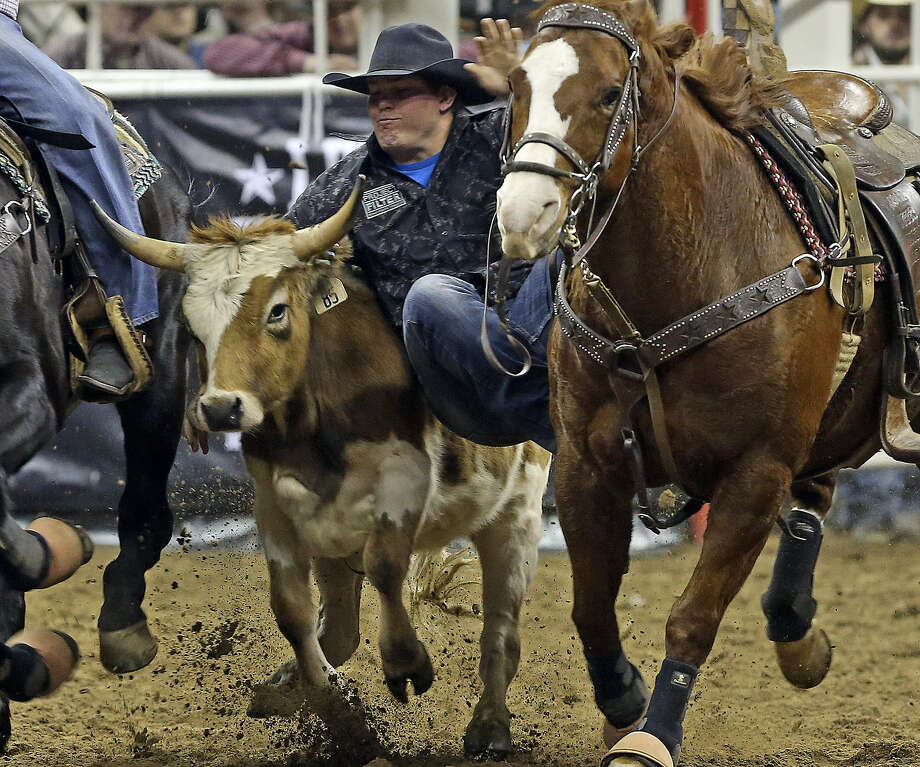 Wyatt Smith takes a steer down in 4.9 seconds at the AT&T Center. It ended up being the second-best time of the evening, enough to earn him $1,473 and push him to $3,438 overall. He will compete in tonight's finals. Photo: Photos By Tom Reel / San Antonio Express-News