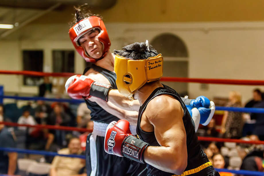 Mason Reina (right) connects to end his bout with Lundberg Garrison in a novice welterweight bout at the San Antonio Regional Golden Gloves event. Photo: Marvin Pfeiffer / San Antonio Express-News