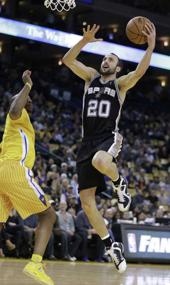 Spurs guard Manu Ginobili takes the ball to basket past the Golden State Warriors' Carl Landry during the first half of Friday night's late game in Oakland, Calif. Photo: Ben Margot / Associated Press