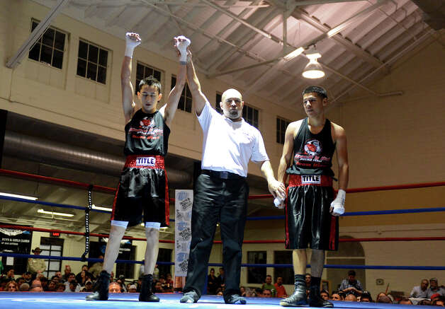 Zachary Enrique is named champion of the Sub Novice Bantam division after defeating Jacob Soto during the San Antonio Golden Gloves tournament at Woodlawn Gym, Friday, Feb. 22, 2013. Photo: JOHN ALBRIGHT, For The Express-News / San Antonio Express-News