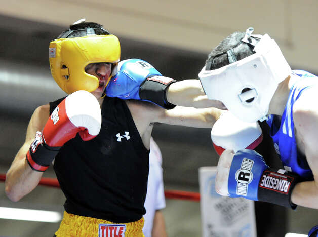 Richard Purrier (right) lands a punch to the face of Marc Salas (right) during the Novice Flyweight Championship during the San Antonio Golden Gloves tournament at Woodlawn Gym, Friday, Friday, Feb. 22, 2013. Photo: JOHN ALBRIGHT, For The Express-News / San Antonio Express-News