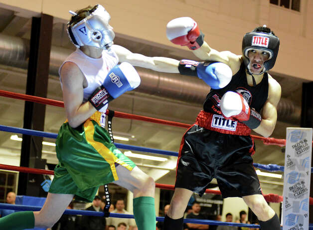 Michael Mendez (right) throws a punch as he fights Daniel Reed (left) during the Sub-Novice Flyweight Championship of the San Antonio Golden Gloves tournament at Woodlawn Gym, Friday, Feb. 22, 2013. Photo: JOHN ALBRIGHT, For The Express-News / San Antonio Express-News