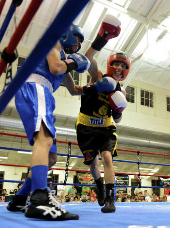 Edson Lozano (right) throws a right hook as he fights Nicholas Garcia (left) during the Sub-Novice Light Flyweight Championship   during the San Antonio Golden Gloves tournament at Woodlawn Gym, Friday, Feb. 22, 2013. Photo: JOHN ALBRIGHT, For The Express-News / San Antonio Express-News