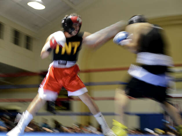 Two fighters throw punches during the San Antonio Golden Gloves tournament at Woodlawn Gym, Friday, Feb. 22, 2013. Photo: JOHN ALBRIGHT, For The Express-News / San Antonio Express-News