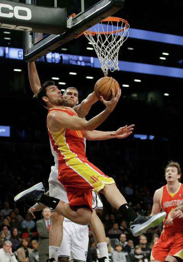 Usually noted for his long-range shooting, Carlos Delfino drives past the Nets' Brook Lopez in his new role as a Rockets starter. Photo: Frank Franklin II, STF / AP