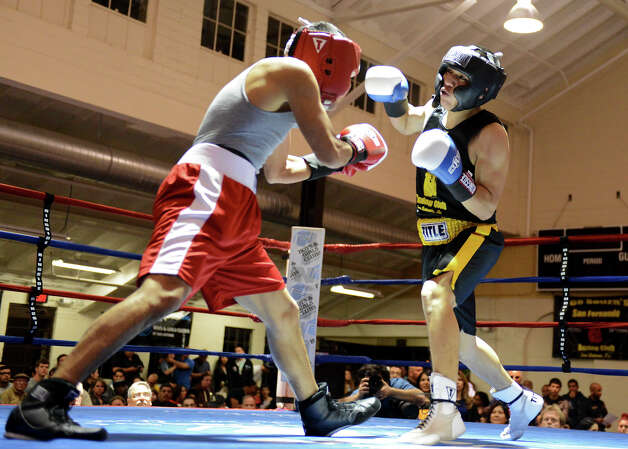 Jose Hernandez (right) throws a punch as he fights Leonal Aguilar (left) during the Novice Light Welterweight Championship of the San Antonio Golden Gloves tournament at Woodlawn Gym, Friday, Feb. 22, 2013. Photo: JOHN ALBRIGHT, For The Express-News / San Antonio Express-News