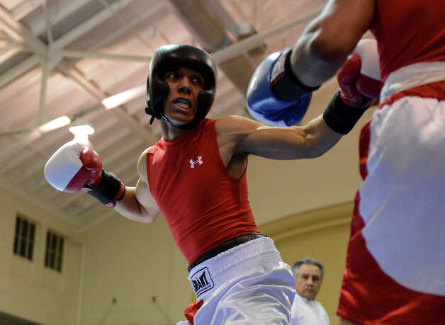 Thomas Toledo throws a punch as he fights Edward Curiel during the Novice Lightweight Championship of the San Antonio Golden Gloves tournament at Woodlawn Gym, Friday, Feb. 22, 2013. Photo: JOHN ALBRIGHT, For The Express-News / San Antonio Express-News