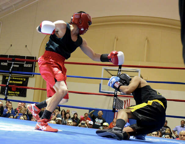 Jose Olivarez (left) throws a punch as Raul Cervantes (right) is knocked out during Sub Novice Lightweight Championship of the San Antonio Golden Gloves tournament at Woodlawn Gym, Friday, Friday, Feb. 22, 2013. Photo: JOHN ALBRIGHT, For The Express-News / San Antonio Express-News