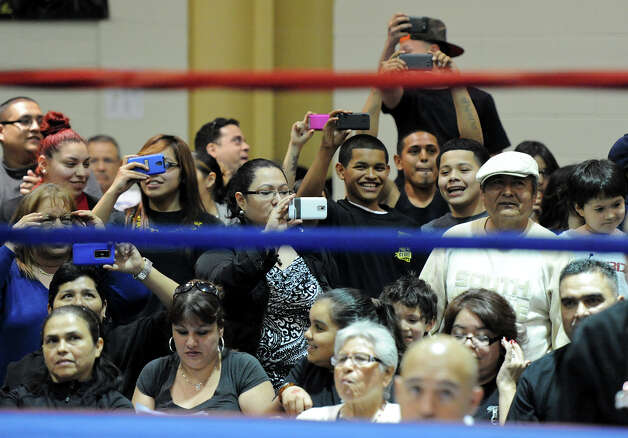 Fans gather around the ring with their cell phones to record a fight during the semifinals of the San Antonio Golden Gloves tournament at Woodlawn Gym, Friday, Friday, Feb. 22, 2013. Photo: JOHN ALBRIGHT, For The Express-News / San Antonio Express-News