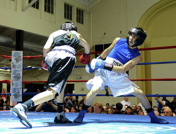 John Moreno (right) ducks a punch by Jade Flores (left) during the semifinals of the San Antonio Golden Gloves tournament at Woodlawn Gym, Friday, Feb. 22, 2013. Photo: JOHN ALBRIGHT, For The Express-News / San Antonio Express-News