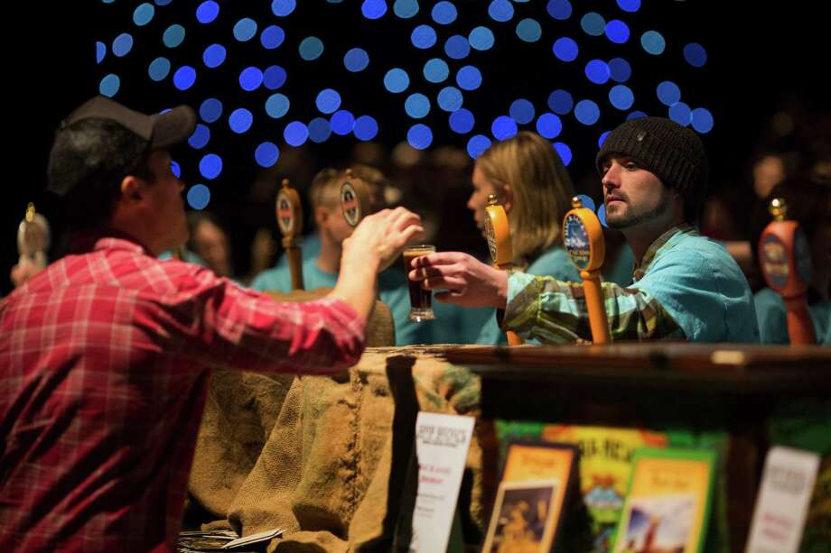 Volunteer Pat Halloran, right, hands a Mac and Jack's African Amber to an attendee. Photo: JORDAN STEAD / SEATTLEPI.COM / SEATTLEPI.COM