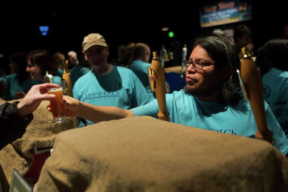 A volunteer hands an attendee a beer. Photo: JORDAN STEAD / SEATTLEPI.COM / SEATTLEPI.COM