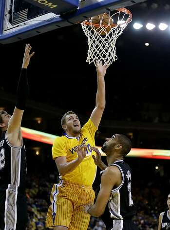 OAKLAND, CA - FEBRUARY 22:  David Lee #10 of the Golden State Warriors shoots over Tim Duncan #21 of the San Antonio Spurs at Oracle Arena on February 22, 2013 in Oakland, California. The Warriors are wearing new short-sleeved uniforms for the first time.   NOTE TO USER: User expressly acknowledges and agrees that, by downloading and or using this photograph, User is consenting to the terms and conditions of the Getty Images License Agreement.  (Photo by Ezra Shaw/Getty Images) Photo: Ezra Shaw, Getty Images