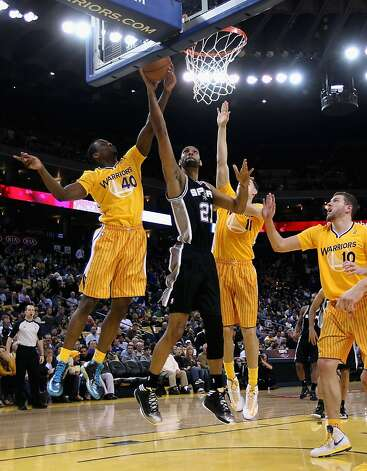 OAKLAND, CA - FEBRUARY 22: Tim Duncan #21 of the San Antonio Spurs goes up for a shot against Harrison Barnes #40 of the Golden State Warriors at Oracle Arena on February 22, 2013 in Oakland, California. The Warriors are wearing new short-sleeved uniforms for the first time. The Warriors won the game in overtime. NOTE TO USER: User expressly acknowledges and agrees that, by downloading and or using this photograph, User is consenting to the terms and conditions of the Getty Images License Agreement.  (Photo by Ezra Shaw/Getty Images) Photo: Ezra Shaw, Getty Images