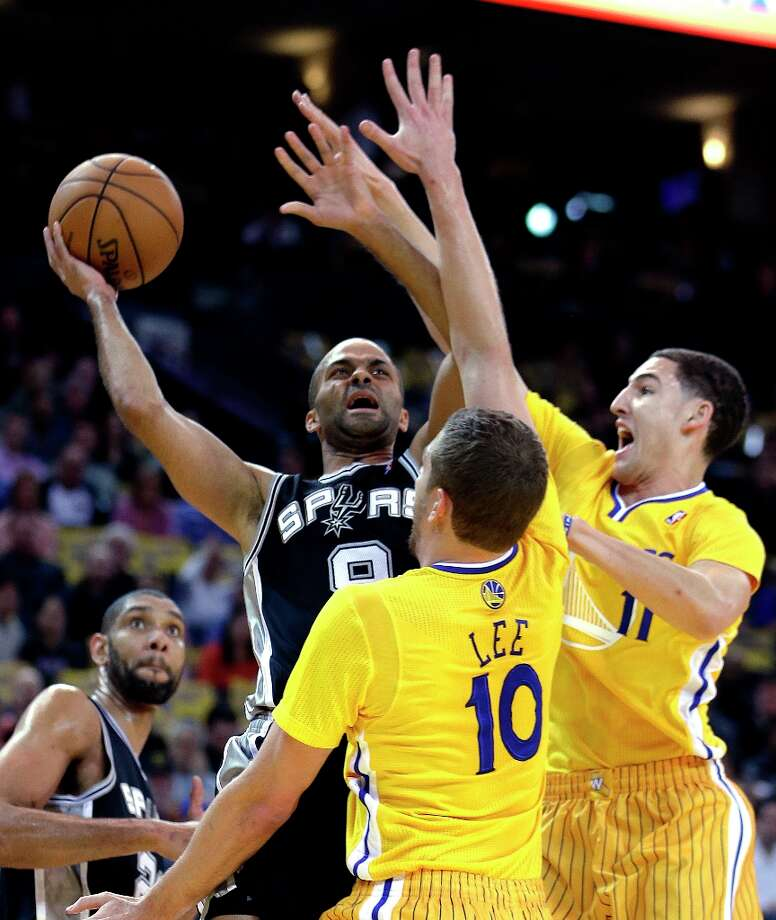 The Spurs' Tony Parker, left, shoots between the Warriors' David Lee (10) and Klay Thompson, right, during the first half  Friday, Feb. 22, 2013, in Oakland, Calif. Photo: Ben Margot, Associated Press / AP