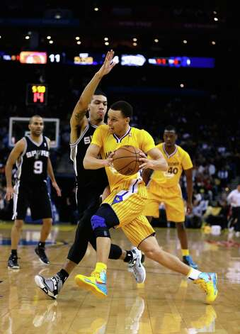 Stephen Curry #30 of the Warriors drives on Danny Green #4 of the Spurs at Oracle Arena on Feb. 22, 2013 in Oakland, California. Photo: Ezra Shaw, Getty Images / 2013 Getty Images