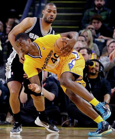 The Warriors' Harrison Barnes (40) drives the ball past the Spurs' Gary Neal during the first half Friday, Feb. 22, 2013, in Oakland, Calif. Photo: Ben Margot, Associated Press / AP