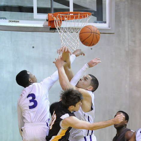 At center, Ryan Hardin  # 10 of Brunswick goes for a rebound against Isiah Hayden, left, and Tim Reitzenmein, both of Masters during the FAA boys high school basketball semifinal between Brunswick School and Masters at Brunswick in Greenwich, Friday night, Feb. 22, 2013. Photo: Bob Luckey / Greenwich Time