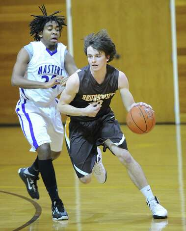 At right, Sam Fraser of Brunswick in action during the FAA boys high school basketball semifinal between Brunswick School and Masters at Brunswick in Greenwich, Friday night, Feb. 22, 2013. Photo: Bob Luckey / Greenwich Time