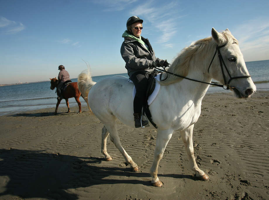 In this file photo, Caroline Sicilian, right of Stamford, and her friend Bonnie Kreither of Fairfield ride their horses at low tide at Penfield Beach in Fairfield. Photo: Brian A. Pounds / Connecticut Post