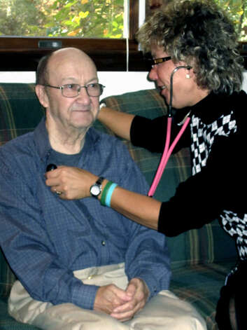Still with plenty of spunk as he experiences hospice care in his home in 2011 from Kathy Leier, Hugh Nuremberg of New Milford does his best to sit still while she conducts basic health checks. Photo: Norm Cummings