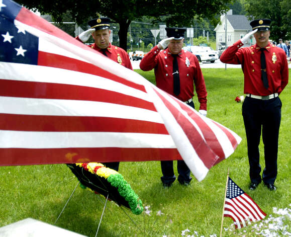 Water Witch Hose Co. No. 2 firefighters, from the left, Todd Russell, Dwayne Acton and Jim Ferlow, offer a heartfelt salute at the war memorial at the south end of the Village Green in New Milford on Memorial Day. 2011 Photo: Norm Cummings