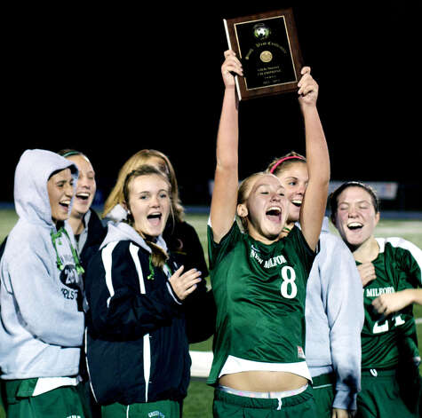 Morgan Gallagher holds the title plaque aloft while joining her teammates in celebration following New Milford High School girls' soccer's 1-0 victory over Newtown in the South-West Conference title match in November 2011. The championship is the first ever league title for either NMHS boys' or girls' soccer. Photo: Trish Haldin