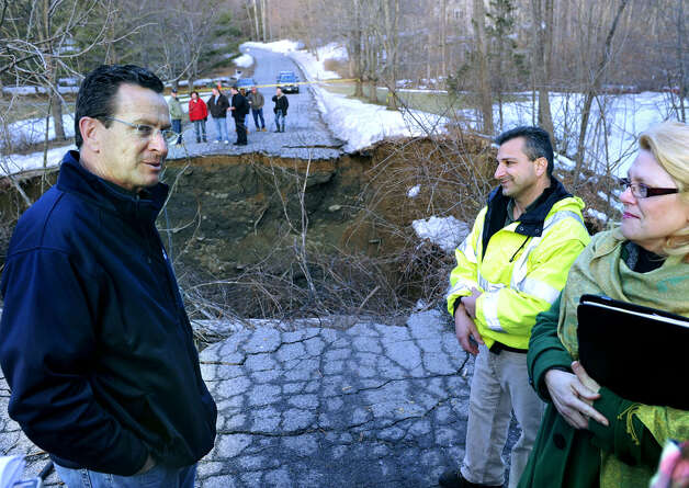 Gov. Dannel Malloy gets a first-hand look in March 2011 at flood damage on Chinmoy Lane in the Merryall district of New Milford. Sharing the experience with the governor are Mayor Pat Murphy and Mike Zarba, the director of Public Works. A large section of the road was washed away by the Merryall Brook early Monday morning. March 8, 2011. Photo: Carol Kaliff