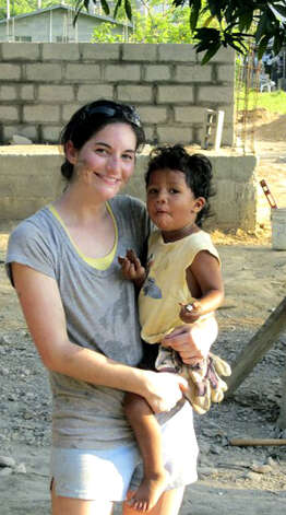 New Milford High School graduate Caitlin Hennessy, a senior at James Madison (Va.)  University in Virginia, poses with young friend Gustavo during her March 2011 trip spent assisting people in Honduras.  Courtesy of Caitlin Hennessy Photo: Contributed Photo