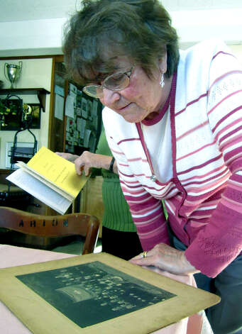 Karla Roder, the membership president of the Arion Singing Society, studies an archival photo as the society prepares in 2011 for its 100th anniversary celebration at 411 Danbury Road (Route 7 South) in New Milford. Photo: Norm Cummings