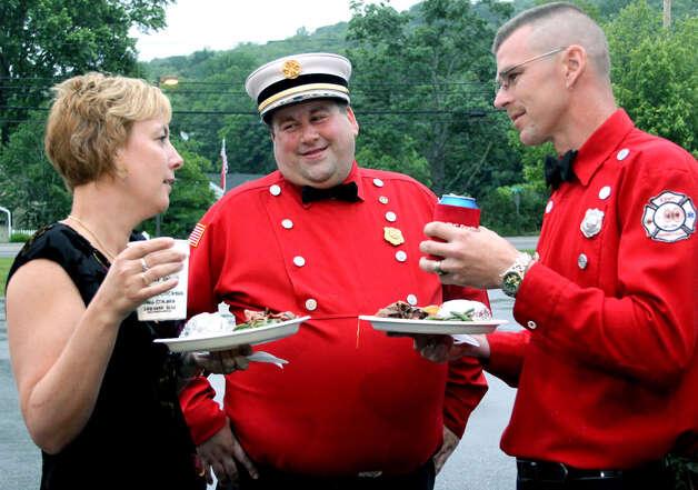 Kent fire Chief Eric Epstein, center, socializes with Cheryl and past assistant chief Jack Kinney at their annual Firemen's Ball, an event marking the firefighters' 100th anniversary of service in Kent. June 11, 2011 Photo: Walter Kidd
