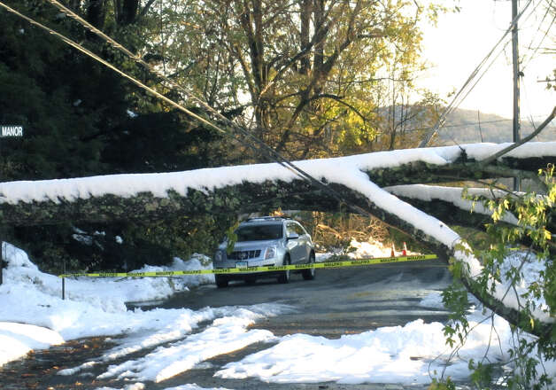 Power lines bow ominously under the weight of a fallen tree lying across Aspetuck Avenue in New Milford in October 2011. Nearby Canterbury School, whose campus was left without power by Storm Alfred, cancelled classes and activities for much of the week. Photo: Norm Cummings