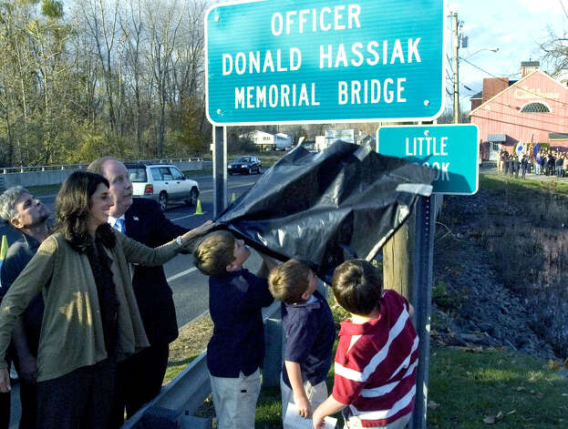 Members of the Hassiak family remove the cover revealing the sign memorializing Donald Hassiak along Route 7 in New Milford on Thursday, Nov. 10, 2011. Donald, a Danbury police officer, was the family patriarch and was killed in a hit-and-run accident while biking to work on June 3, 2010. The Hassiak family from left: Kimberly Duff Hassiak, and sons Matthew, 9; D.J., 6; and Luke, 8. Photo: Jason Rearick / The News-Times