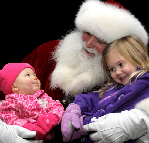 Three-month-old Carina Taylor appears to have captured the heart of Santa Claus while her sister, Mikayla, 3, is simply happy as can be sitting on the lap of Jolly St. Nicholas during the Village Center Organization's Festival of Lights celebration, held Nov. 26, 2011 on the Village Green in New Milford. Photo: Walter Kidd