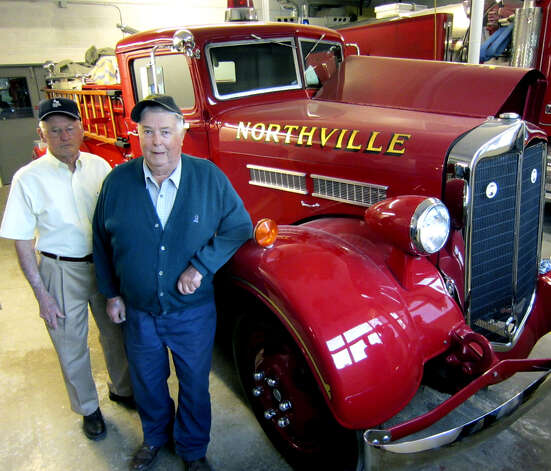 Charter members Charlie Chapin, left, and Maurice Grossenbacher stand proudly with the 50-year-old Northville Volunteer Fire Department's first tanker. April 2012 Photo: Norm Cummings