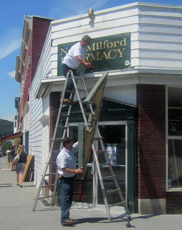 Workers engage Aug. 9, 2012 in taking down the sign for New Milford Pharmacy at the corner of Main and Bank streets in the New Milford village center. The impending move of the Big Y Pharmacy from the site to its Kent Road home will at least temporarily end more than 80 years of the town having a pharmacy at that downtown spot. Photo: Norm Cummings