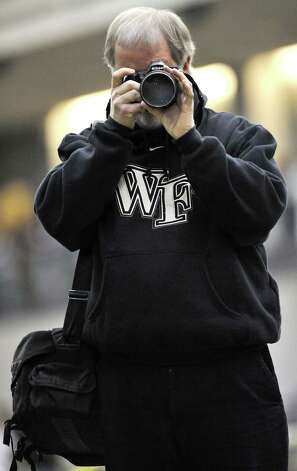 Spectrum photographer Norm Cummings does his best to  focus on the action at the South-West Conference indoor track meet in New Haven. Feb. 7, 2009  Courtesy of John Cheng Photo: Contributed Photo
