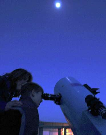 "Exploring the cosmos, Michelle Murphy of New Milford assists her son, Timothy, 7, as he takes a closer look  at Saturn, located in the evening sky near the moon, through a telescope on the skydeck of the John J. McCarthy Observatory on the New Milford High School campus. The Murphys were in attendance as the observatory participated in the International Year of Astronomy's ""100 Hours of Astronomy."" Spectrum/After Cathy Setterlin of New Milford gets assistance with a spinning demonstration from Isabella Gimenez, Ms. Setterlin ties a woven bracelet onto the seven-year-old's wrist at Sunny Valley Preserve's Open Farm Day held Sept. 17, 2011 in New Milford. Photo: Deborah Rose"
