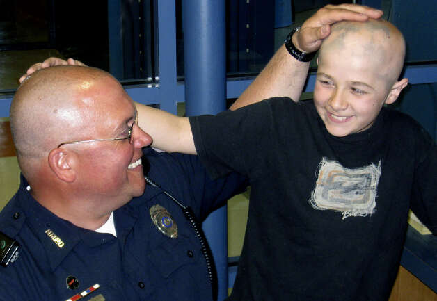 School resource officer Kevin O'Neill of the New Milford Police Department has shown his support for Sarah Noble Intermediate School fifth-grade student Vincent Galanti, 10, by shaving off his hair. Vincent is battling the disease alopecia areata, and has lost much of his own hair. April 21, 2009  Photo by Norm Cummings Photo: Norm Cummings