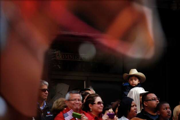 Aydan Gallegos, 3, of Houston gets a good look at the 2013 Downtown Rodeo Parade while on his father's shoulders Saturday, Feb. 23, 2013, in Houston. Photo: Johnny Hanson, Houston Chronicle / © 2013  Houston Chronicle