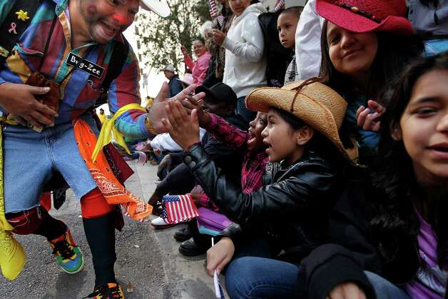 A rodeo clown gives high-fives to parade attendees on Walker Street during the 2013 Downtown Rodeo Parade Saturday, Feb. 23, 2013, in Houston. Photo: Johnny Hanson, Houston Chronicle / © 2013  Houston Chronicle